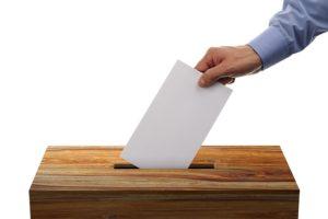 Η εικόνα εμφανίζει ένα χέρι που ρίχνει ένα φάκελο μέσα σε μια ψύλινη κάλπη